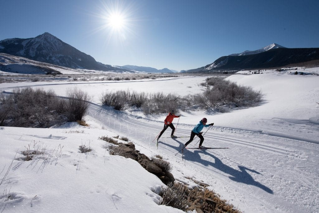Skate skiers on a groomed trail with Mt Crested Butte in the background