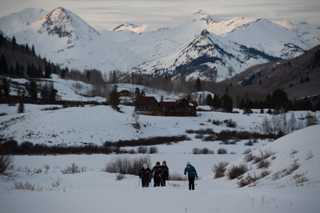 Crested Butte Nordic junior team training on snow with Paradise Divide in background