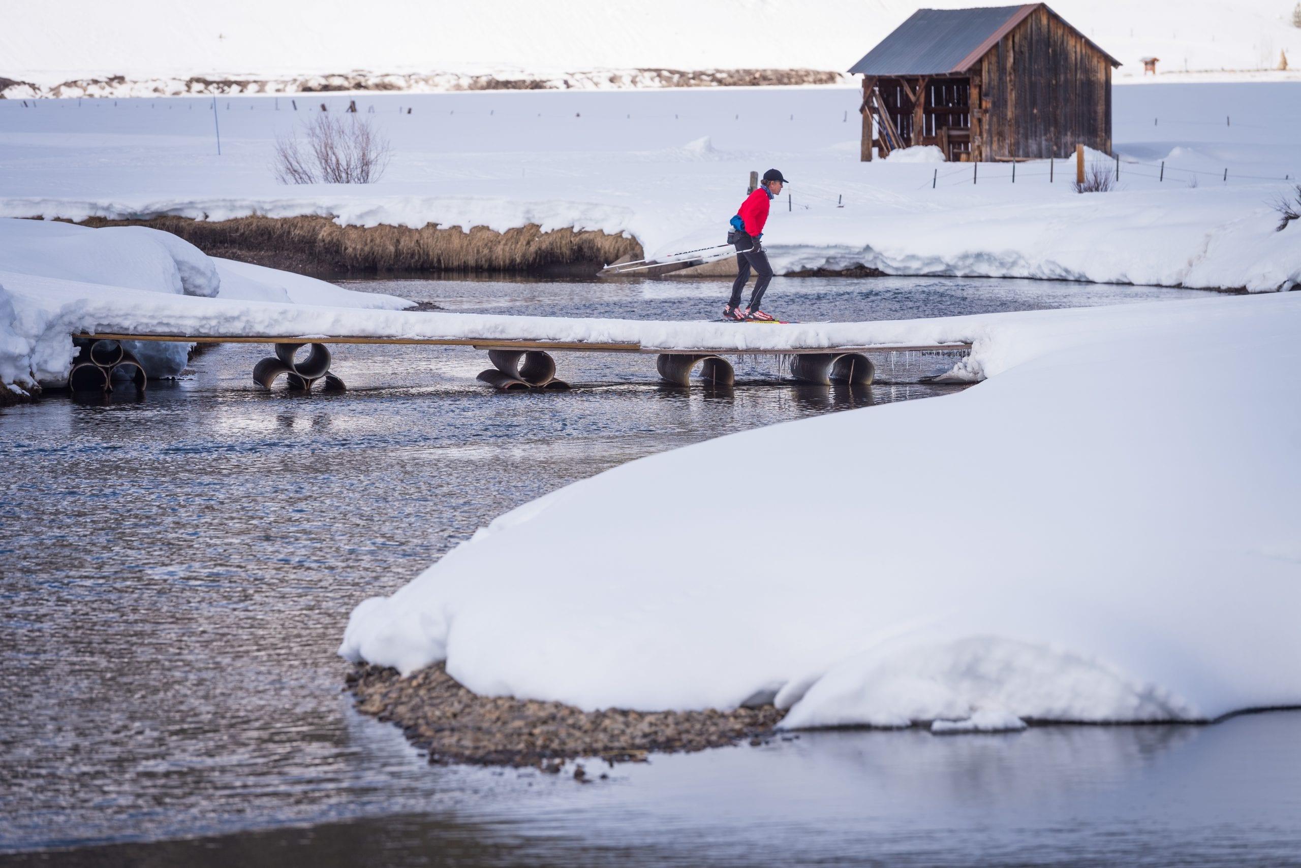 Solo skier crossing a bridge in early season