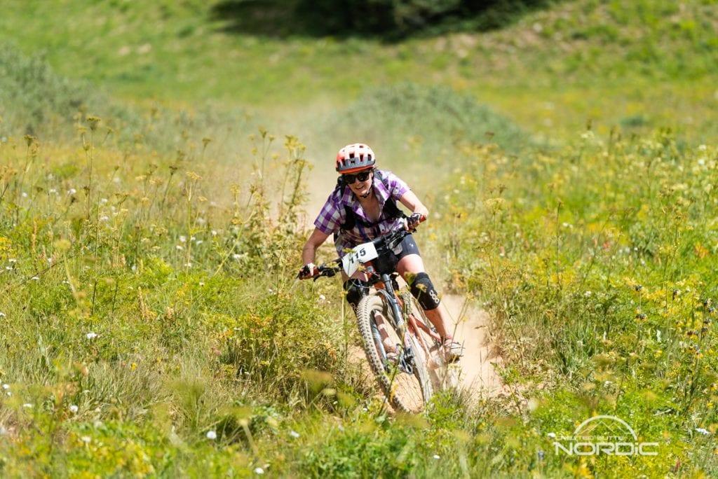 Grand Travers biker on a downhill through a wildflower meadow