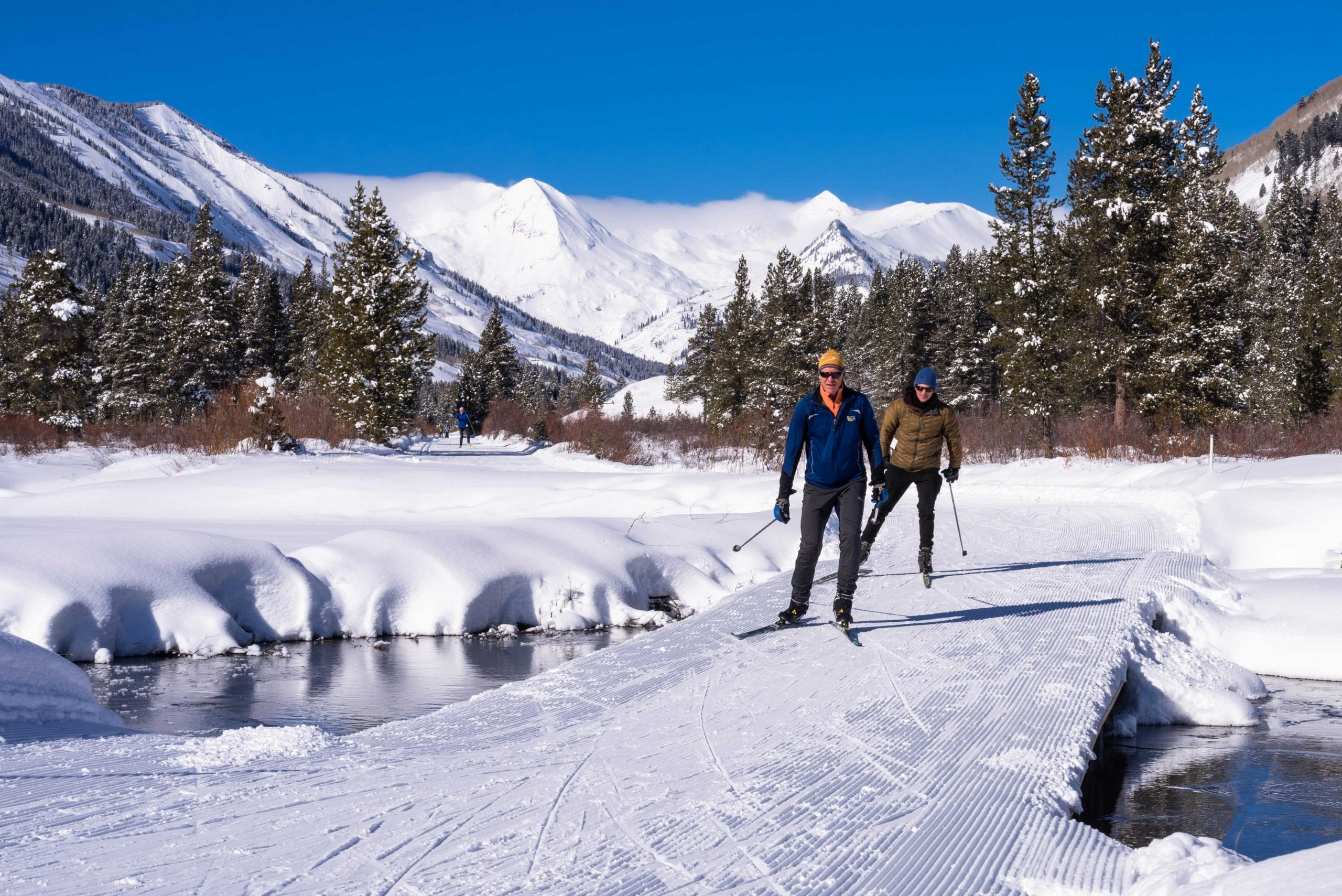 Skate skiers crossing a bridge over Slate River on Mike's Mile