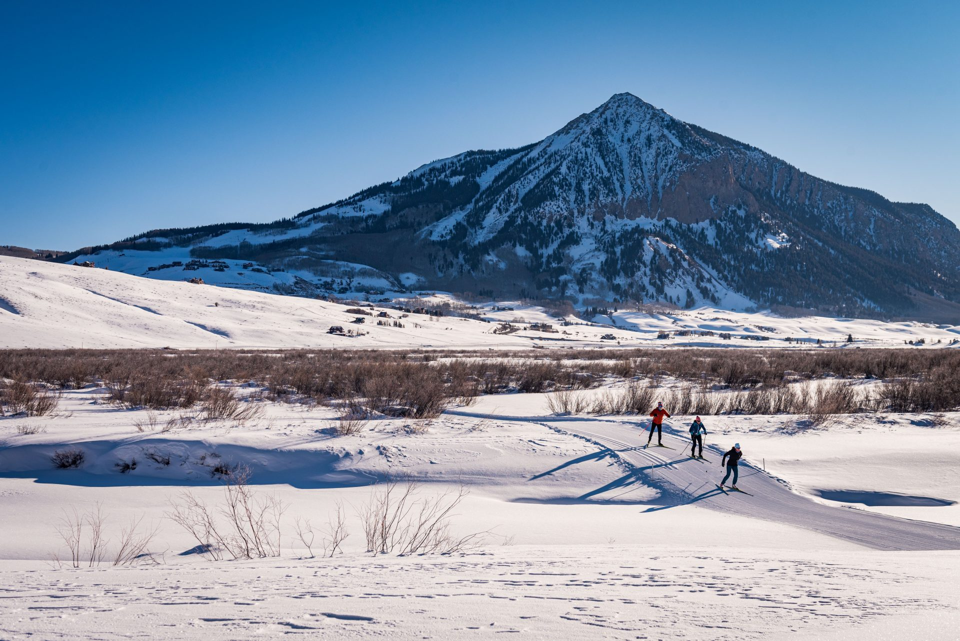 Skiers on Peanut Lake trails with Mt Crested Butte in background