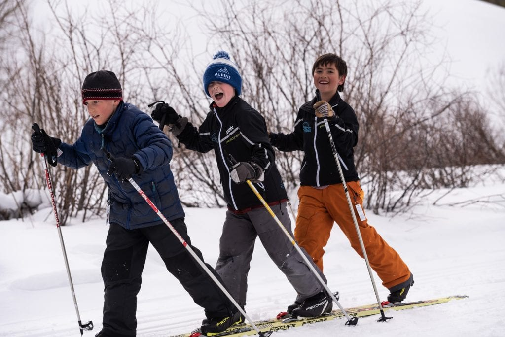 Three young skiers coordinating movement on a triple mounted pair of skis