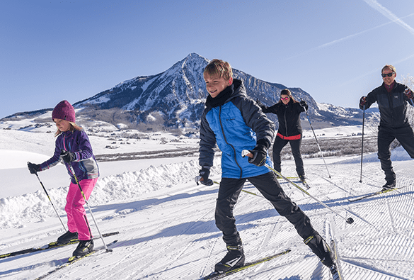 Family out for a skate ski with Mt Crested Butte in background