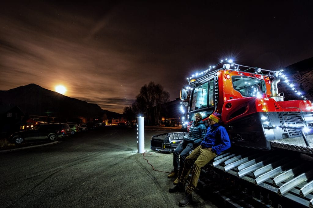 Community members connecting at annual potluck near lit up snow cat