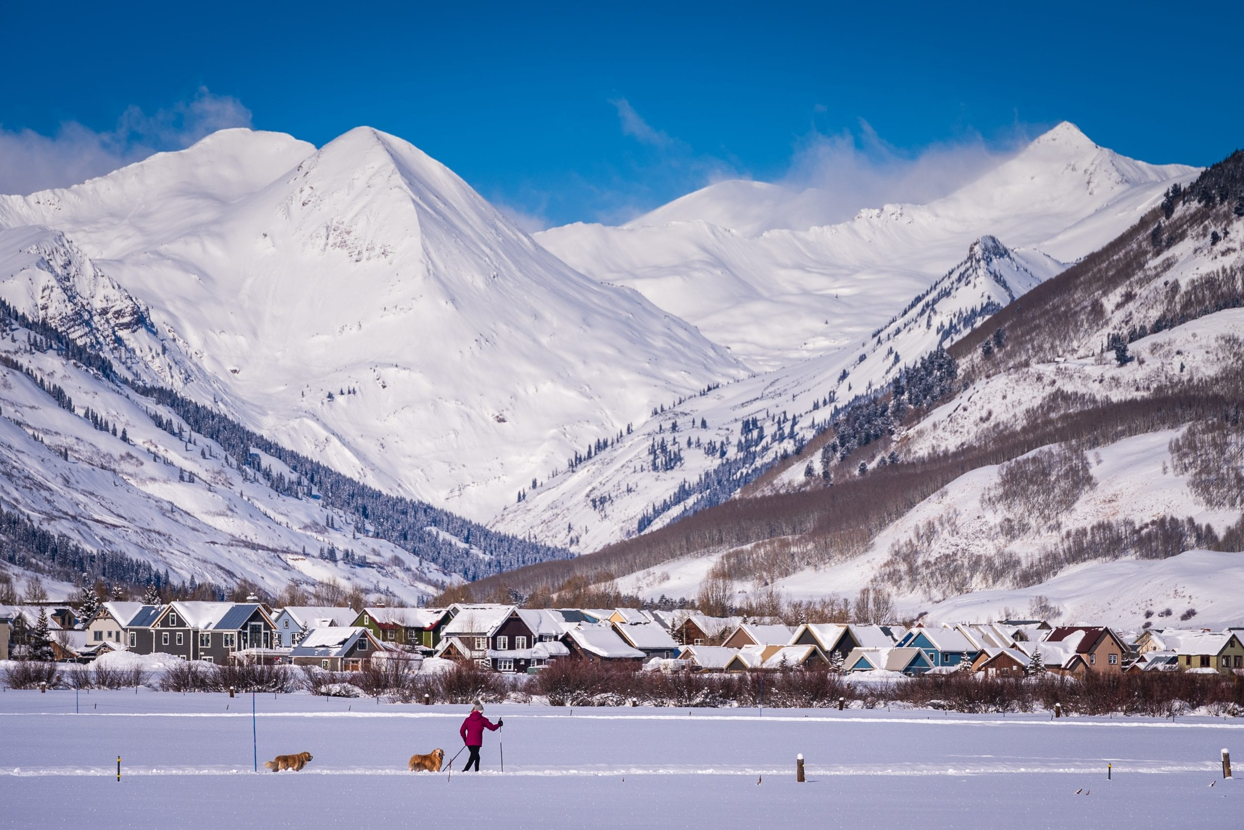 Skier and dogs with CB town and Paradise Divide backdrop