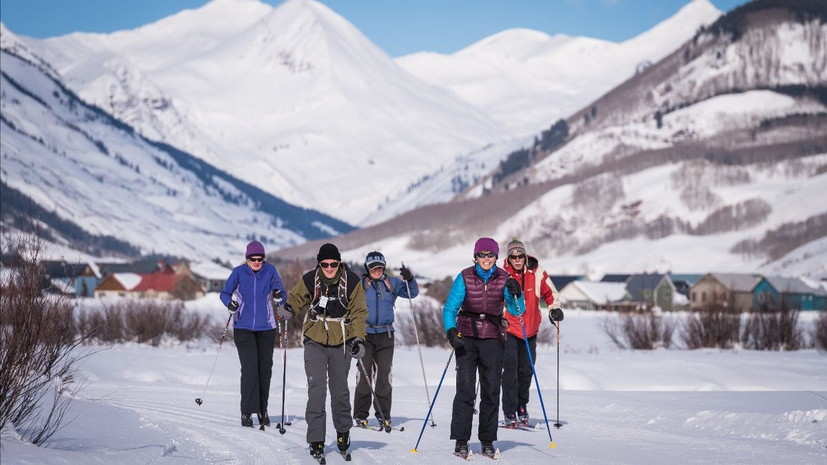 Gray Hares group skiing on Town Ranch trails with Paradise Divide backdrop