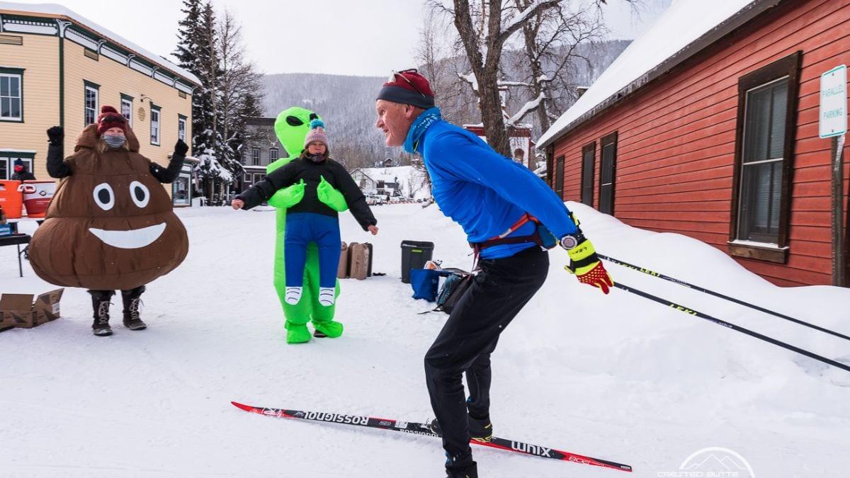 Alley Loop skier being cheered on by costumed spectators