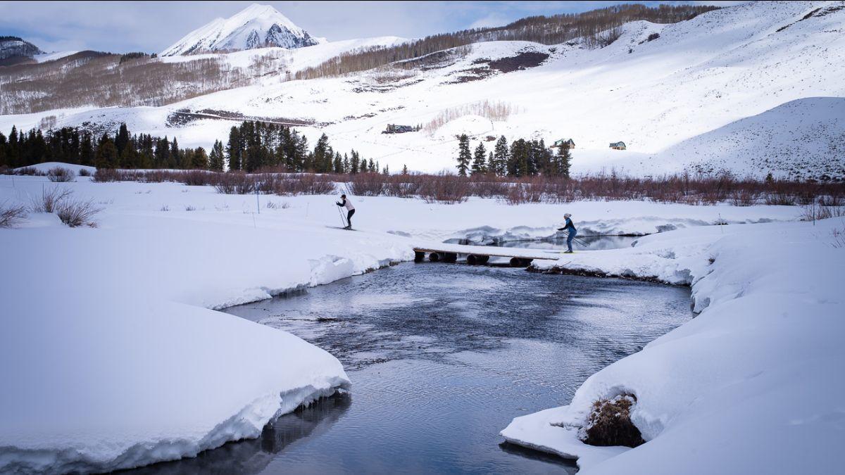 Skiers crossing a bridge near Peanut Lake outside Crested Butte